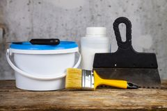 Items for home or office renovation. Against a gray wall. Paint can and brush on the table royalty free stock photography