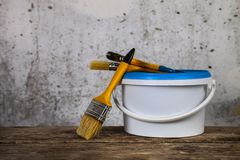 Items for home or office renovation. Against a gray wall. Paint can and brush on the table stock photography