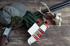 Items for hunting with deer skull. Top view. Hunting shotgun with deer skull and clothes. Top view Stock Photography