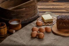 Items and ingredients for baking on a wooden background. Flour, eggs, rolling pin, whisk, sieve, butter, bread Royalty Free Stock Images