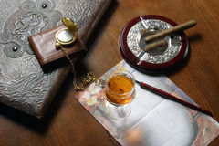 Items of luxury. Several items indicating luxury and sophisticated elegance on a desktop including a glass of whiskey, leather wallet, and gold pocket watch Stock Image