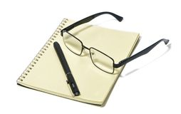 Items for the office, still life, Glasses, modern pair of glasses, black rim, note pad, pen. Office supplies, accessories, office, work, stationery royalty free stock images