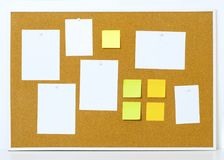Items pinned to a cork message board with wood frame. Yellow stick notes. royalty free stock photo