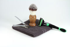 Mens Shaving and Grooming Items. Items for a simple or rugged mens grooming and shaving. Items include razor, nail clippers, towel, and shaving cream royalty free stock photos