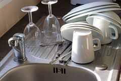 Items on a sink draining board. Plates,mugs and wine glasses on a draining board by a domestic sink. Items are left to air dry on the drainer before being put Stock Images