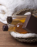 Items for Spa treatments, personal hygiene. Chocolate soap, body oil, shampoo, body wash   in a basket   and   towel nearby Royalty Free Stock Photo