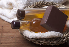 Items for Spa treatments, personal hygiene. Chocolate soap, body oil, shampoo, body wash   in a basket   and   towel nearby Stock Images