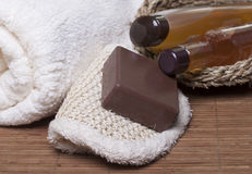Items for Spa treatments, personal hygiene. Chocolate soap on a white sponge, body oil, shampoo, gel   for body  in a basket and towel nearby Royalty Free Stock Photography