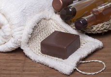 Items for Spa treatments, personal hygiene. Chocolate soap on a white sponge, body oil, shampoo, gel   for body  in a basket and towel nearby Stock Photos
