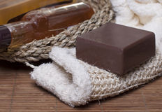 Items for Spa treatments, personal hygiene. Chocolate soap on a white sponge, body oil, shampoo, gel   for body  in a basket and towel nearby Stock Image