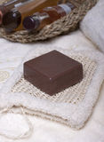 Items for Spa treatments, personal hygiene. Chocolate soap on a white sponge, body oil, shampoo, gel   for body  in a basket and towel nearby Royalty Free Stock Photos