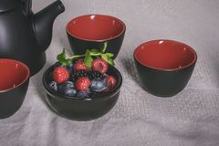 Items for tea on the table, black and red cups with black-red be. Rries Stock Images