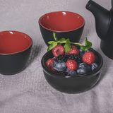 Items for tea on the table, black and red cups with black-red be. Rries Stock Photos