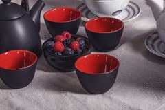 Items for tea on the table, black and red cups with black-red be. Rries Royalty Free Stock Photography
