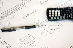 Items on technical drawing. A view of a calculator and pen sitting on technical drawings Royalty Free Stock Photos