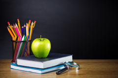 Items to take to school. School items including colored pencils and crayons, a spiral note book, text book, magnifier and an apple on a wooden table stock images