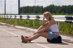 Itenerant attractive woman. The girl, travelling  hitch-hiking, sits on a flank Royalty Free Stock Photo