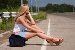 Itenerant attractive woman. The girl, travelling  hitch-hiking, sits on a flank Royalty Free Stock Photos