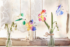 Iterior window with glass butterflies and snowdrops. Fragment of interior on old windowsill with little glass vials, blossom snowdrops and four glass butterflies Stock Photo