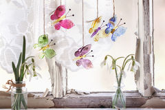 Iterior window with glass butterflies and snowdrops. Fragment of interior on old windowsill with little glass vials, blossom snowdrops and four glass butterflies Stock Images