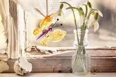 Iterior window with glass butterfly and snowdrops. Fragment of interior on old windowsill with little glass vials, blossom snowdrops and glass butterfly. See Royalty Free Stock Image