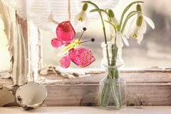 Iterior window with glass butterfly and snowdrops. Fragment of interior on old windowsill with little glass vials, blossom snowdrops and glass butterfly. See Stock Photo