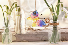 Iterior window with glass butterfly and snowdrops. Fragment of interior on old windowsill with little glass vials, blossom snowdrops and glass butterfly. See Royalty Free Stock Photos