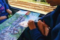 Itinéraire trainlooking se reposant de voyage de carte de sac à dos de voyageuse de femme Photographie stock libre de droits