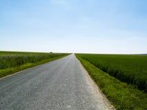 Itinerario e cielo blu rurali. Immagine Stock