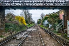 Itinerario ferroviario con un piccolo ponte pedonale immagini stock libere da diritti