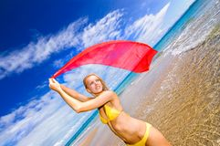 Its all about colour. Lady in yellow bikinis with red scarf, crystal clear ocean water deep blue skies and a warm summer day Stock Image