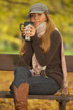 Its Autumn! 2. 20-25 years old beautiful sexy woman portrait in natural autumn outdoors. Sitting on park bench with cup of coffee Stock Photos