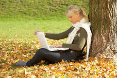Its Autumn!. 20-25 years old beautiful sexy woman portrait working on laptop computer in natural autumn outdoors Stock Photo