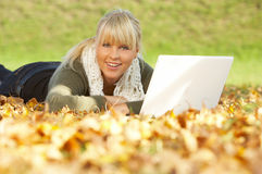 Its Autumn!. 20-25 years old beautiful sexy woman portrait working on laptop computer in natural autumn outdoors Royalty Free Stock Photos