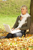 Its Autumn!. 20-25 years old beautiful sexy woman portrait working on laptop computer in natural autumn outdoors Stock Photos