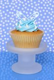 Its A Boy. Birth of a boy cupcake on stand with diaper pins - blue spotty background Royalty Free Stock Image