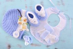 Its a Boy Baby Shower or Nursery background. Its a Boy Baby Shower or Nursery layout with bonnet, booties, socks and pacifier and dummy on pale blue shabby chic royalty free stock image