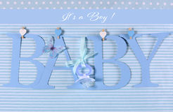 Its a boy, blue theme Baby bunting letters. Under from pegs on a line for nursery, greeting card or baby shower stock image