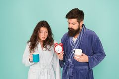 Its coffee time. Every morning begins with coffee. Couple in bathrobes with mugs. Man with beard and sleepy woman enjoy. Morning coffee or tea. Guy in bath royalty free stock photography
