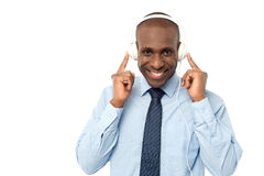 Its really fantastic to hear songs !. Happy male executive enjoying songs with earphones stock image