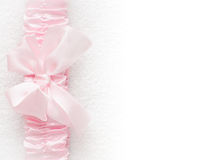 Its a girl - baby announcement or invitation. Pink satin bow and ribbon forms a side border over the soft white texture which fades into copyspace Stock Images