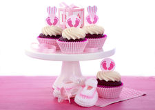 Its a Girl Baby Shower Cupcakes. With baby feet toppers and decorations on shabby chic pink wood table Royalty Free Stock Image