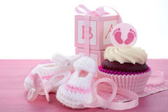 Its a Girl Baby Shower Cupcakes. With baby feet toppers and decorations on shabby chic pink wood table Royalty Free Stock Photography