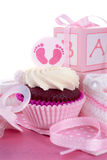 Its a Girl Baby Shower Cupcakes. With baby feet toppers and decorations on shabby chic pink wood table Stock Photo