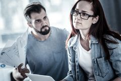 Thoughtful bespectacled woman sitting and looking aside. Its happen again. Thoughtful bespectacled redhead women sitting in the bright room near angry men Royalty Free Stock Photography