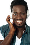 Its music time. Young man listening to music through headphones, closeup shot Stock Photos