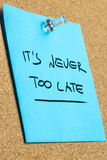 Its Never Too Late Phrase on Pinned Sticky Note. Conceptual Its Never Too Late Phrase on a Light Blue Sticky Note Pinned on the Cork Board, Captured in Close up Royalty Free Stock Photography