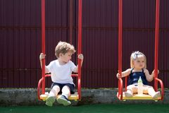 Its a nice childhood. Small children with blond hair on swing. Girl and boy haircut styles. Small brother and sister. Enjoy playing together. Hair salon for stock photography