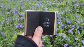 Its Spring time idea. Book with text and spring field with blue flowers. stock video footage