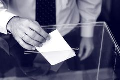 Its time for elections. Image of a ballot box and hand putting a blank ballot inside, elections concept stock image